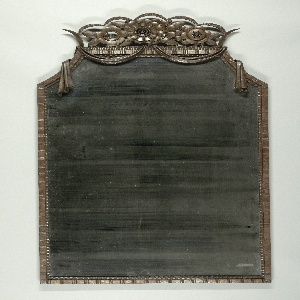 Simple frame with incised line and thumb indention type decoration; uprights concave at top; top decorated with swags and stylized flowers. Mirror has bevelled edge.
