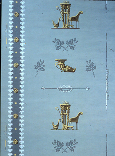 A scene containing an altar, Grecian chair and staff alternates with a boars' head vessel. Sprigs of oak leaves and acorns are interspersed. To the left runs a blue stripe with floral bosses. Printed in blue, ocher, brown and white on blue ground.