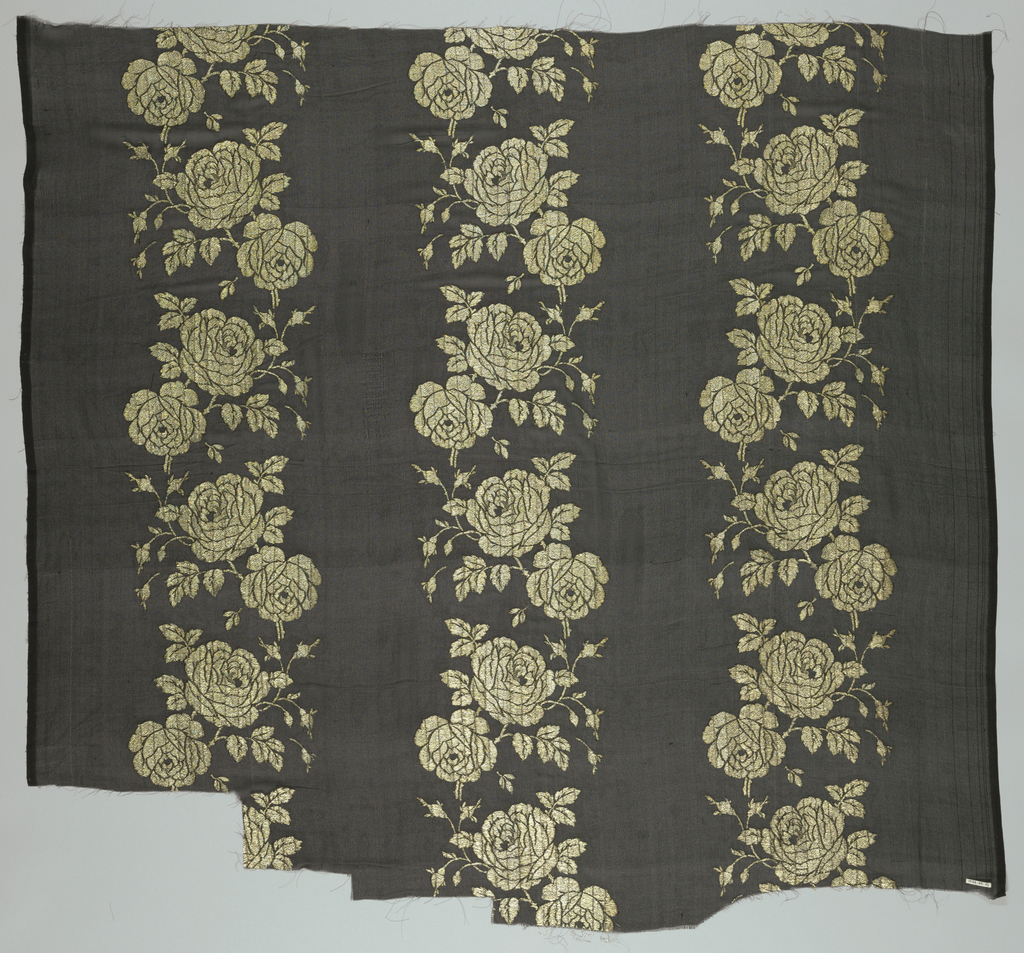 Black ground with gold brocaded design. Three vertically-running serpentine columns of roses. Both selvedges present.