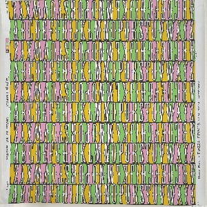 The alphabet, A through Z, printed in rows, alternating between right-side up and upside down. Printed in green, pink and ocher on white ground. Children's paper.