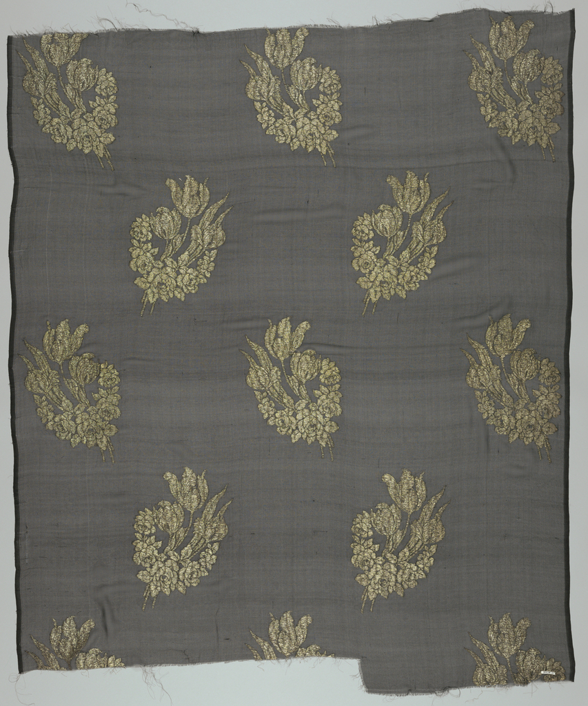 Black ground with large-scale repeat spotted over groun, of garland of roses with several tulips, in gold brocade. Both selvedges present.