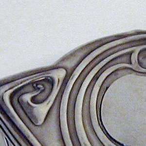 Flat, irregular shape; lid hinged at back side.  Relief decoration on sides and lid of curving lines with whiplash terminals.