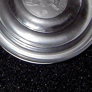 Flattened circular shape, sides ribbed, lid fits snugly over base;engraved  in circular medallion on top of lid is a stylized dog.