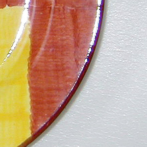 Circular form with narrow rim.  Brushed underglaze decoration of light brown field with three overlapping squares in dark brown, orange, and yellow; thin dark brown band around rim.