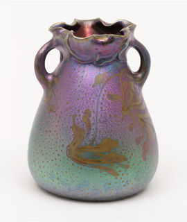 Buff-gray clay body, molded. Slightly bulbous body, tapering to neck with crimped molded leaf rim; two small curved handles at shoulder to rim; no foot. Design on front and back of honeysuckle blossoms and vines against a random dot pattern painted in gold. Iridescent background shades from a blue-green to a lavender-purple towards the shoulder. Interior covered with lustrous copper-red glaze. Bottom glazed a greenish-yellow high glaze; unglazed foot rim. Cracklature. Two-handled