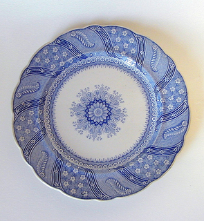 Scalloped-edge plate with blue transfer-printed decoration. Central abstract flower motif with elaborate decorative surround. Border of scrolling bands with geometric motifs, between which are alternating Japaness flower motifs and neoclassical-like motifs with large acanthus leaf.