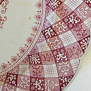 "Red and white plate with ""gingham"" design around rim and a geometric design in center."