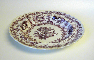 Scalloped-edge shallow bowl with overall purple transfer-printed decoration resembling coral with various flowers and foliate motifs on white ground.