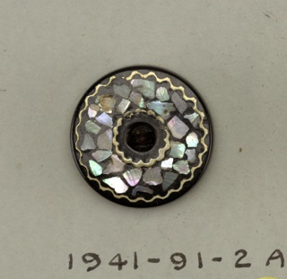 Two circular buttons each with two holes for sewing and ornamented on top with bits of mother of pearl between wavy lines of brass. These two buttons originally part of components making up 1941-91-2-a/f.  See 1941-91-2-b,c and -e for other components which are deaccessioned.  On card 2