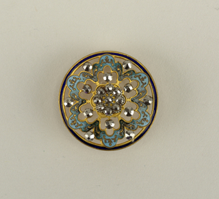 Button of brass, cut-out design with ornaments of steel and enamel. -a: central ornament of cut-steel surrounded by six-lobed figure in blue enamel with brass decoration. Brass shank.