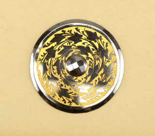 Flat, circular button with beveled edges; in the center, a facetted steel boss; surrounded by ivy leaves, in steel, against, a yellow ground.  Component -b is on card 2