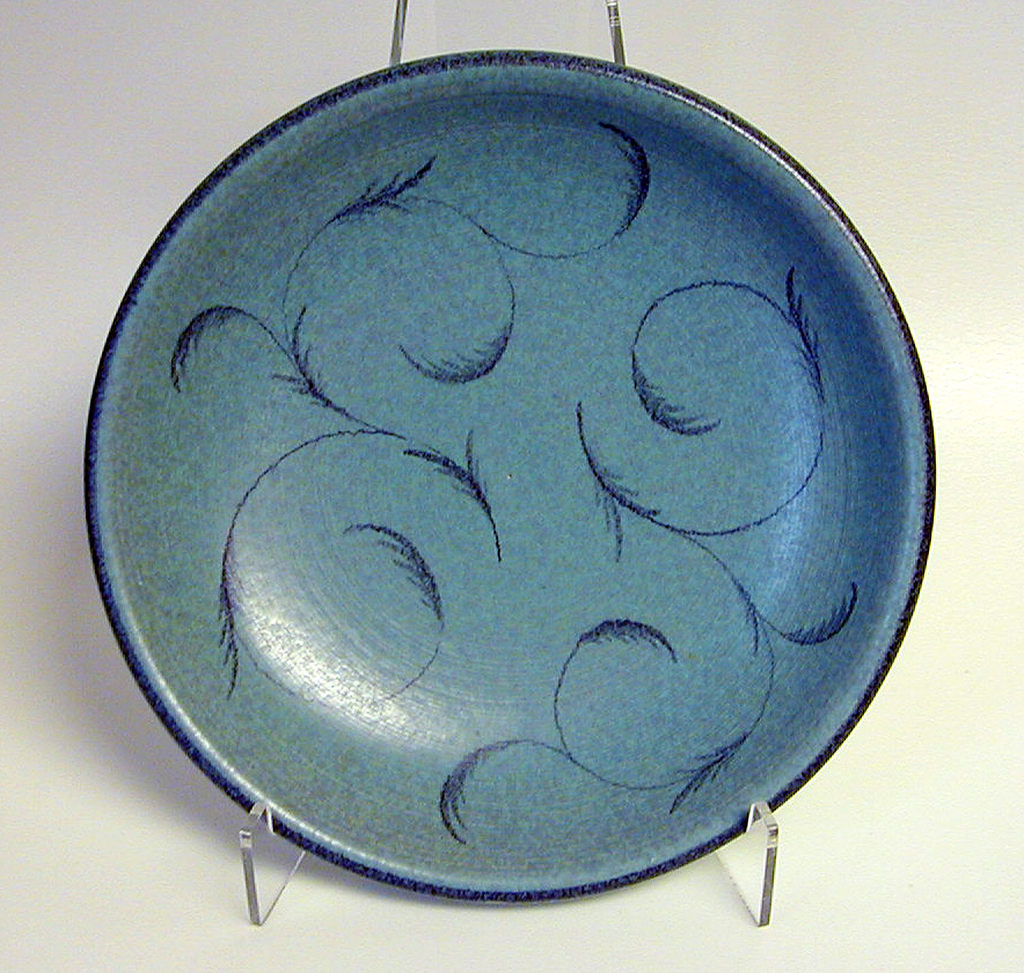 Blue plate with a dark blue rim. Curled feathers decorate the center of the plate in the same dark blue.