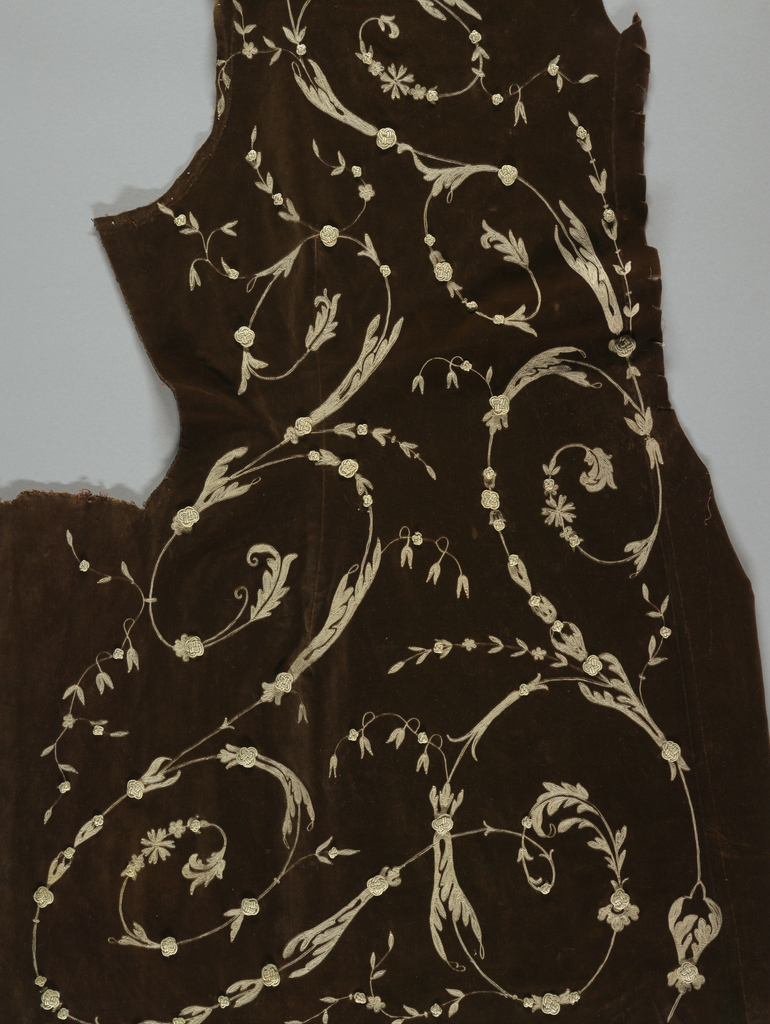 Shaped coat of brown cotton velvet, lining, collar and sleeves removed; embroidered in slender, trailing curved vine design in white. Small knots of white applied as accents. Coat is cut to fit in at waist with cutaway effect at front, slight flare at back; embroidery is designed to fit shape of coat.