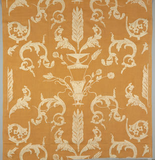 A vertically symmetrical design with axis of mirror imaging in center of vases and curving leaves printed in white on a tan/orange foundation fabric.