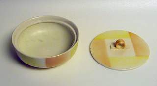 Low bowl on ring foot. Flat lid with loop knob. Pale orange and yellow checkerboard glaze.
