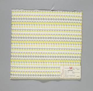 White warp and weft with supplementary weft in white, yellow and silver, forming diamonds, squares and triangles. Serged on two sides and cut on two sides.
