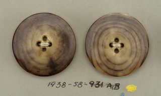 4 circular buttons of bone showing brown concentric rings; four holes for sewing.  Components -a,-b are on card 2 Component -i is on Cooper Union Exhibition card 4
