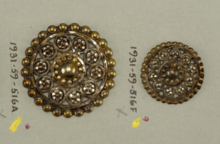 brass button in cut-out design of balls and rosettes arranged in concentric rings.  On card 64