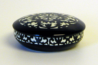 Circular box and slightly domed lid, the arabesque decoration in underglaze black on white; interior in underglaze black.