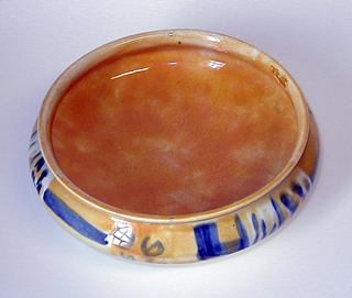 Squat circular form with flaring lip, the bulging body on three curving pyramidal feet.  White ground decorated with mottled golden yellow on interior and exterior; passages of blue lines, spirals and splotches on exterior.