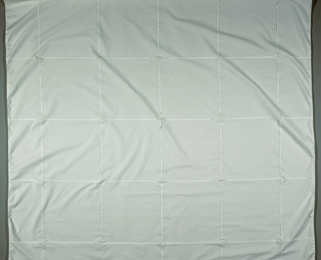 White fabric with small pleats sewn in a square pattern