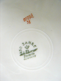 Round white plate with flat marli. Light orange line of glaze at rim and partial circle of bright orange glaze within.