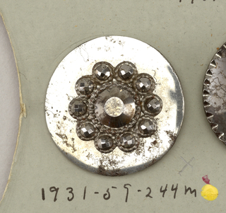 Steel button decorated with faceted steel ornaments, all have a central boss and one of two rings of bosses surrounding it; all have scalloped edge except F,H,K,L,M,N.  On card 65