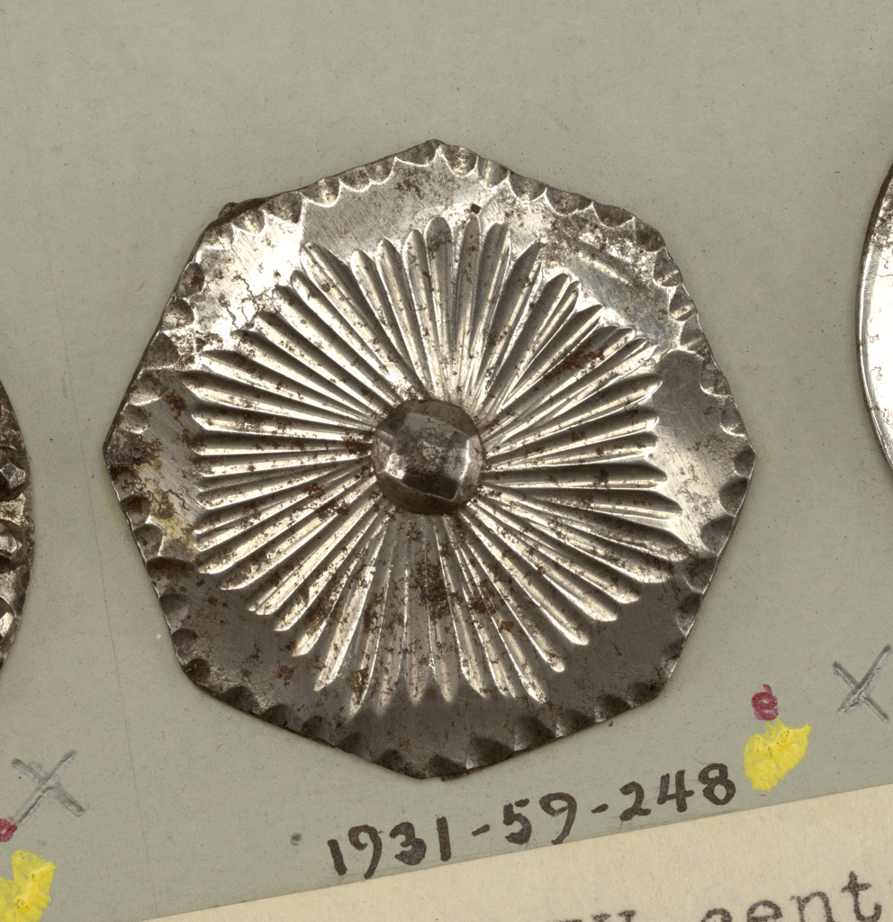 Octagonal button ornamented with gouges at edge and rays arranged around a central boss. Steel shank.