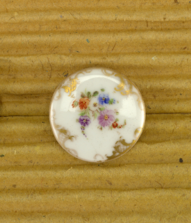 White ceramic buttons with floral motif and gold scroll design at edges, matches 1993-104-5/7
