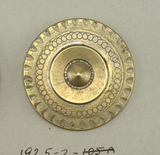 Circular button with central ornament surrounded by a plain raised band, a ring of engraving, and a notched edge.