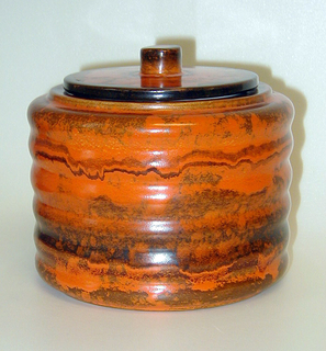 Orange, cylinder body with waved sides and brown accents. The lid is flat with a solid cylinder handle.