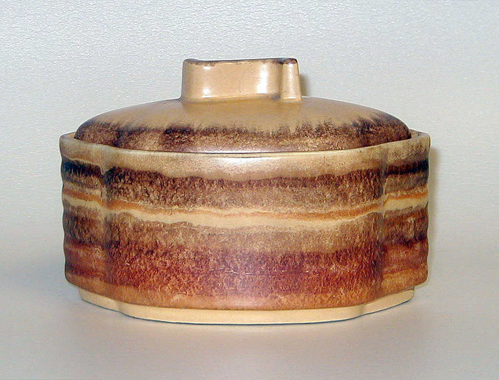 Short, waved cylinder body with a slightly rounded lid. The handle is a raised curved line. The colors are browns, reds and beige.