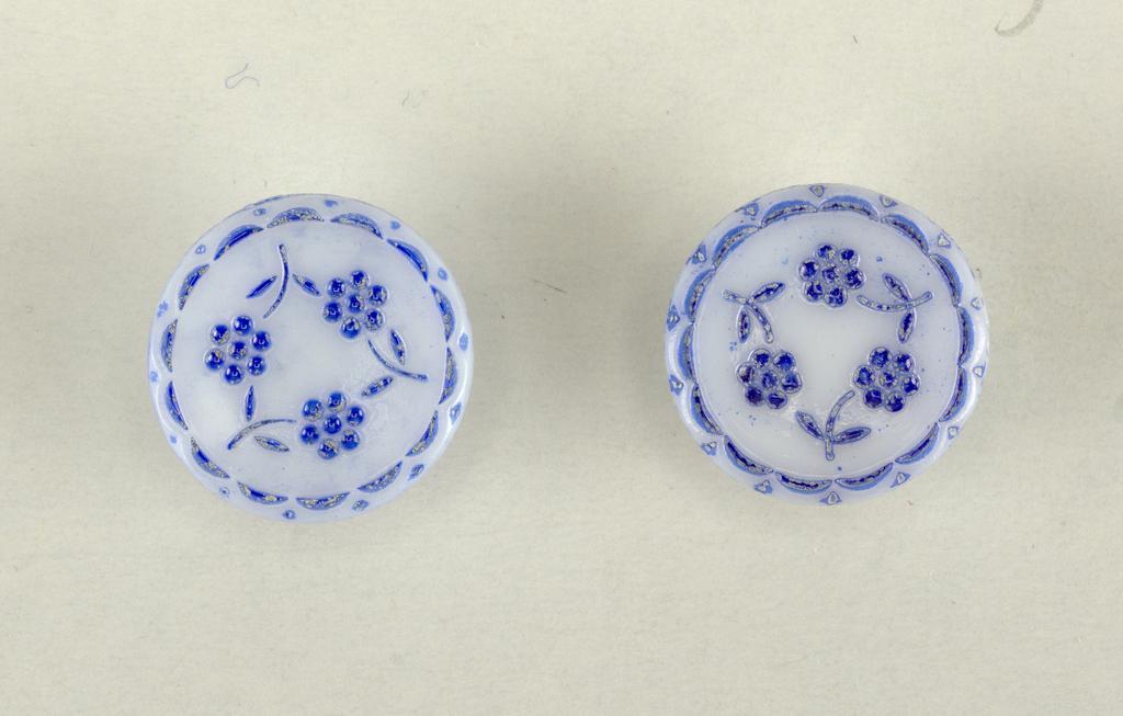 Circular, white glass with blue painted floral and border motif