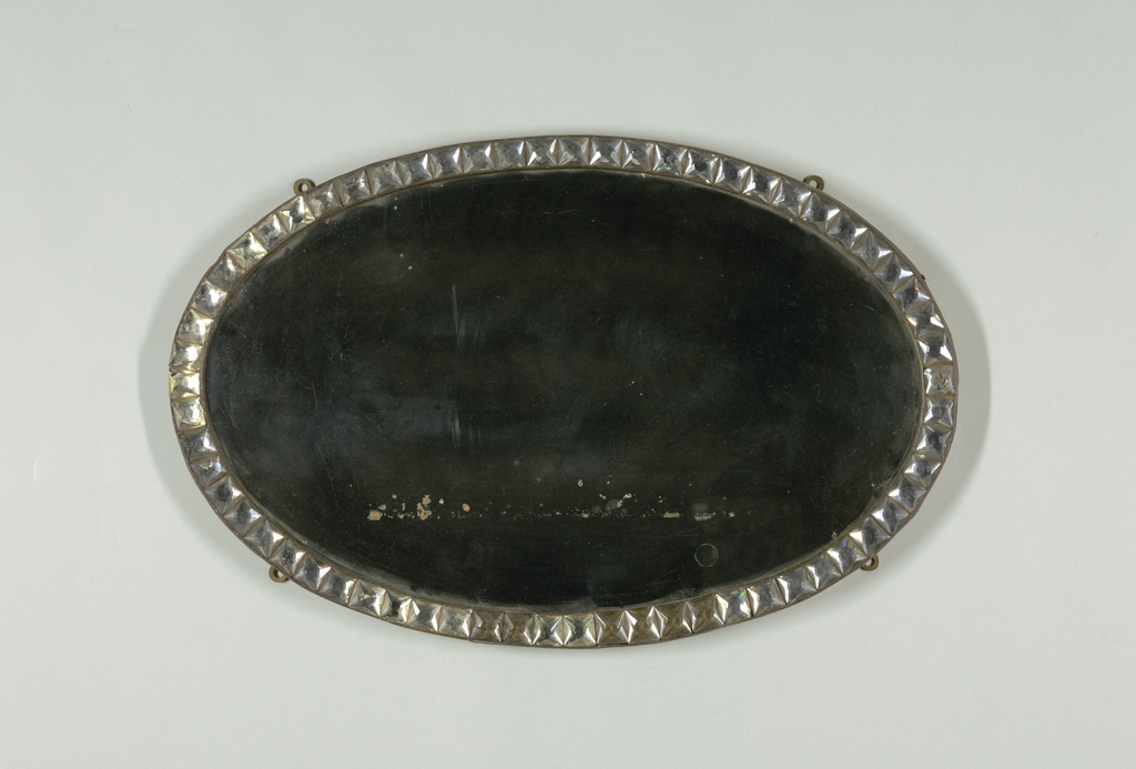 "Oval mirror surrounded by oval metal frame with row of square, faceted glass ""jewels""; wood backing; four mounting rings on reverse, allowing vertical or horizontal orientation."