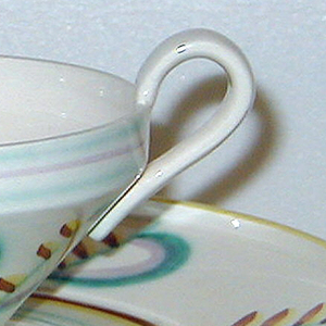 The cup is conical with a flat base and a small looped white handle. Around the rim is has faint blue and purple stripes. The body has an alternating pattern of blue and purple curved lines and red and yellow stripes. The saucer has a similar alternating pattern, although it is spaced further apart.
