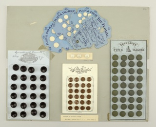 "White card holding 24 black, circular, two-holed buttons in four collumns; top of card with printed trademark: a belt with words ""Rubber Buttons, Goodyear, 1851."", surrounding the initials I. R. C. Co.