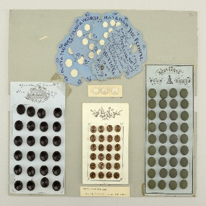 """White card holding 24 black, circular, two-holed buttons in four collumns; top of card with printed trademark: a belt with words """"Rubber Buttons, Goodyear, 1851."""", surrounding the initials I. R. C. Co.  On card i80-2"""