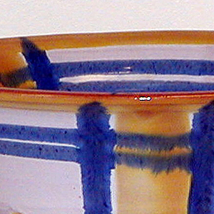 Deep bowl with an orange rim and 3 orange vertical stripes on both the inside and  outside. The orange is blocked in by two vertical blue stripes and two horizontal blue stripes  that extend all the way around the bowl. It is held up by 3 branchlike feet that are more  connected to the body than the ground.
