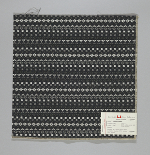 Black warp and weft with supplementary wefts in black, grey and silver metallic, forming diamonds, squares and triangles. Serged on two sides and cut on two sides.