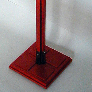 Square base; tall post composed of T- and H-shaped wooden beams, four projections at top, each with metal knob on side.  Base, post and beams painted orange.