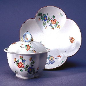 """Sauce boat with lid and tray.  Four-lobed, decorated with insects and branches of blossoms in the """"Korean"""" style.  Rim of tray decorated with brown band. Cover with handle of three petunia-like flowers, and notched for ladle."""