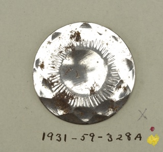 flat, circular buttons with ornament representing ten petalled flower, conventionalized.