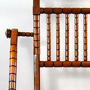 Patented chair with black incised bamboo-look frame, with woven cord seat, vertical slat pierced back, the underseat frame of two demi-lune arches descending to the stretcher.