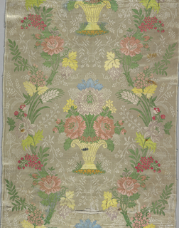 Ground of white satin ornamented with small vine pattern. Brocaded pattern in colored silks of a basket with flowers between serpentine floral bands.
