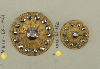 brass buttons with cut steel knobs set in wheel-shaped ornaments.  Components a,c are on card 64