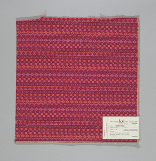 Red warp and weft with supplementary weft in orange, pink and pink metallic, forming diamonds, squares and triangles.  Serged on two sides and cut on two sides.