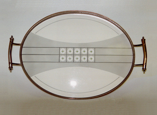 Oval flat ceramic mounted with a metal frame.  Metal oval tray with stand-up sides with cut-out slits sitting on four feet with one handle curving out from each end.  Center decorated with a white ground patterned by a gray band in the center with three darker gray horizontal lines that come to form a grid pattern containing white circles with green centers surrounded by four blue dots.  Also, running along each side is a thin curving gray line.
