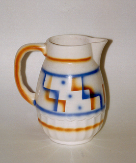 Bulbous form with inset bottom rim, scalloped body bottom, circular band at mouth, and a c-shaped handle sitting across from a spout coming off of the mouth.  White background with lines of airbrushed orange near bottom of body, on bottom of mouth, and on the handle.  Central design of blue dots and steps of blue and orange contained in horizontal blue lines.