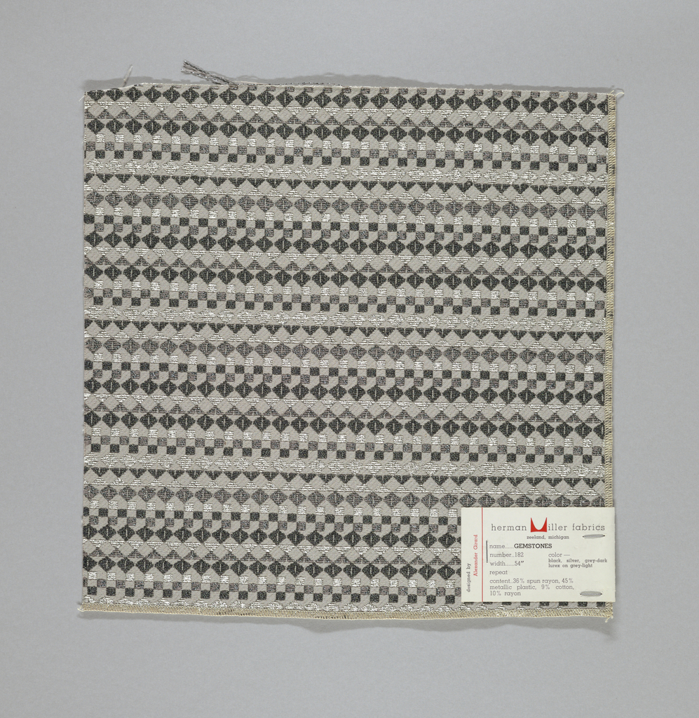 Grey warp and weft with supplementary wefts in black, grey and silver metallics, forming diamonds, squares and triangles. Serged on two sides and cut on two sides.