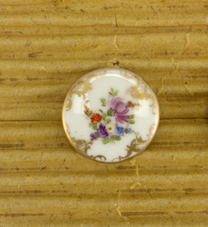 White ceramic buttons with floral motif and gold scroll design at edges, matches 1993-104-6/8